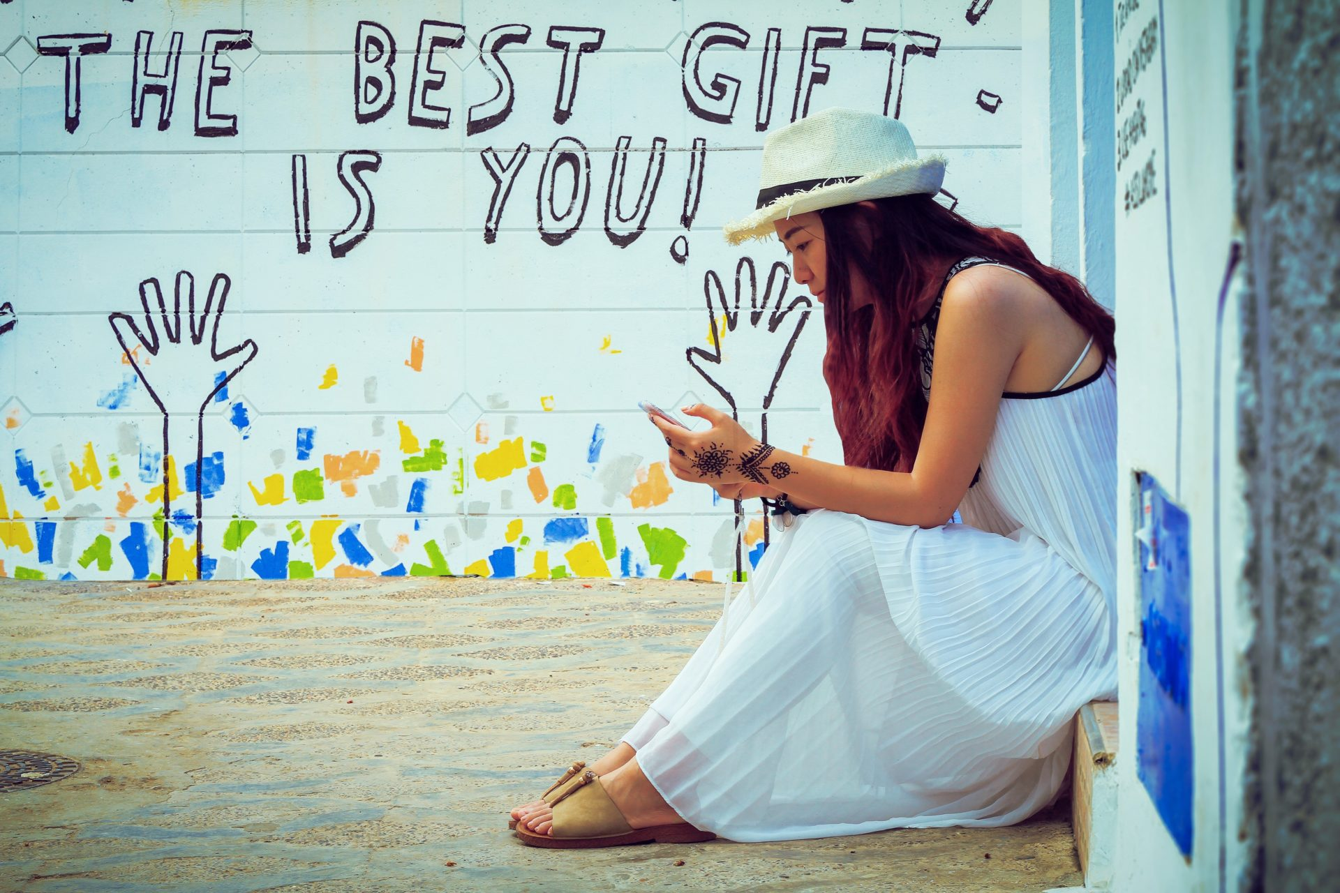 Girl in a long white dress with a white woven fedora sitting on some steps looking at her phone with a mural in the background that says