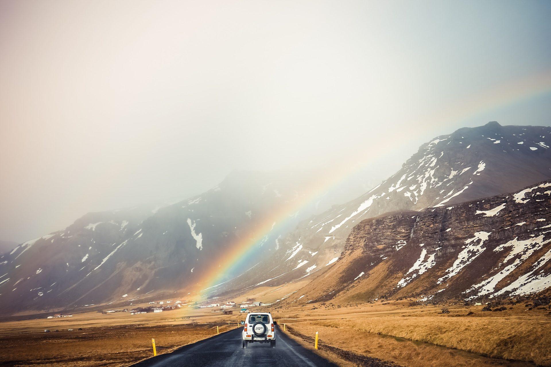 Jeep Driving Under Rainbow