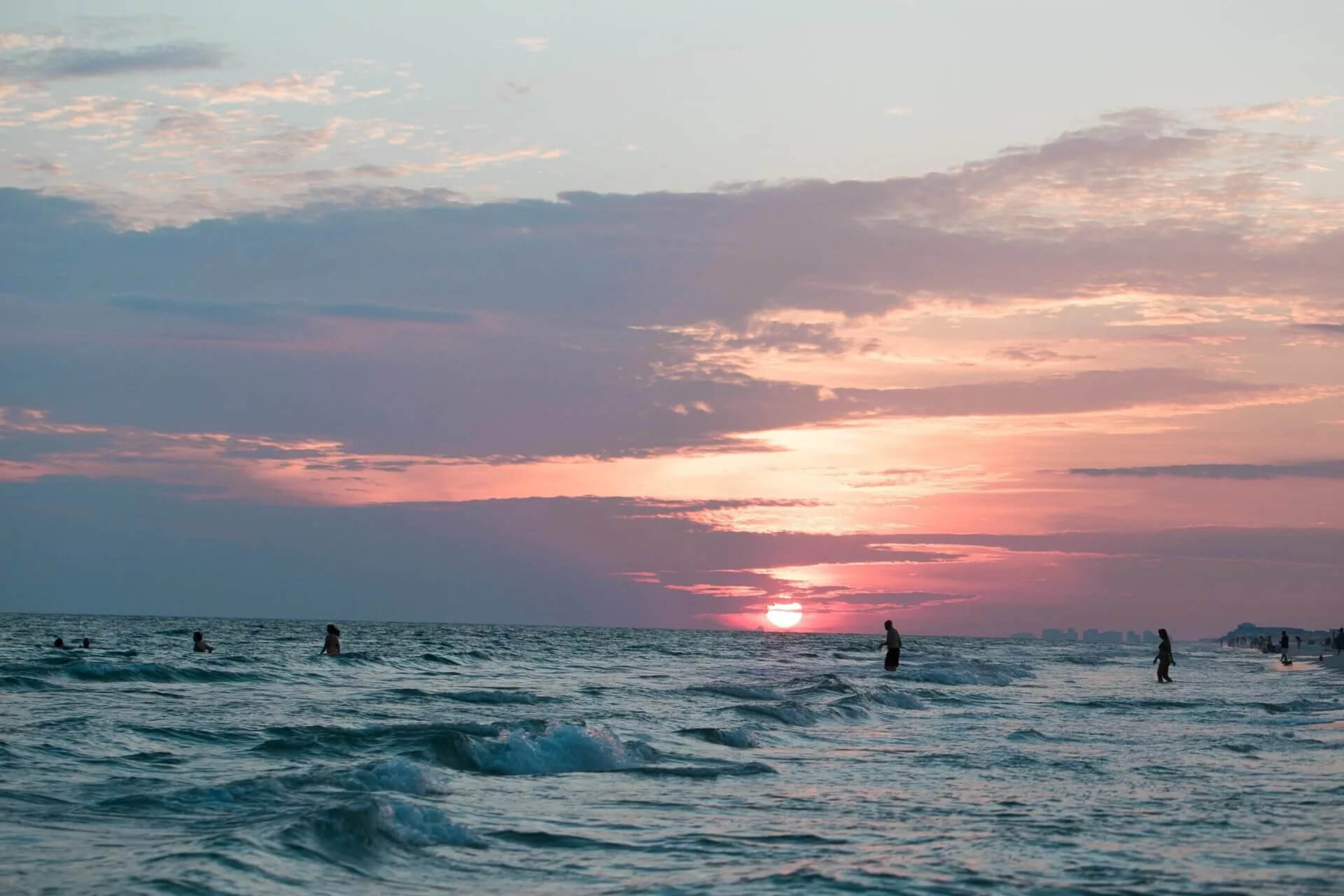 People Swimming in Ocean at Sunset