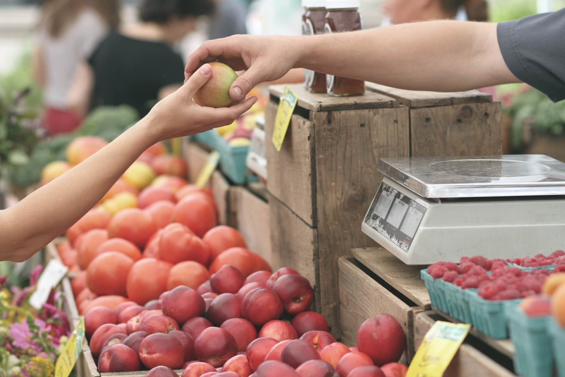 Person Handing Over Apple at a Market, and Another Person Receiving It
