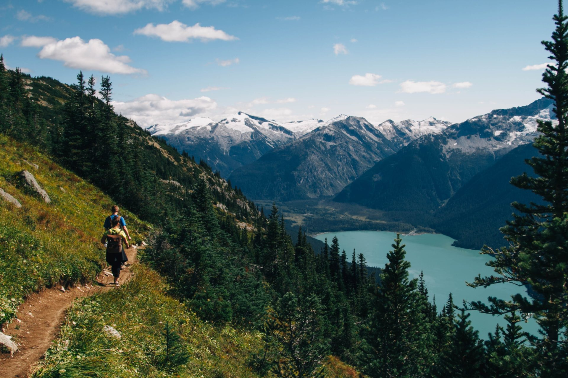 People Walking on Trails Alongside a Mountain Overlooking a Lake