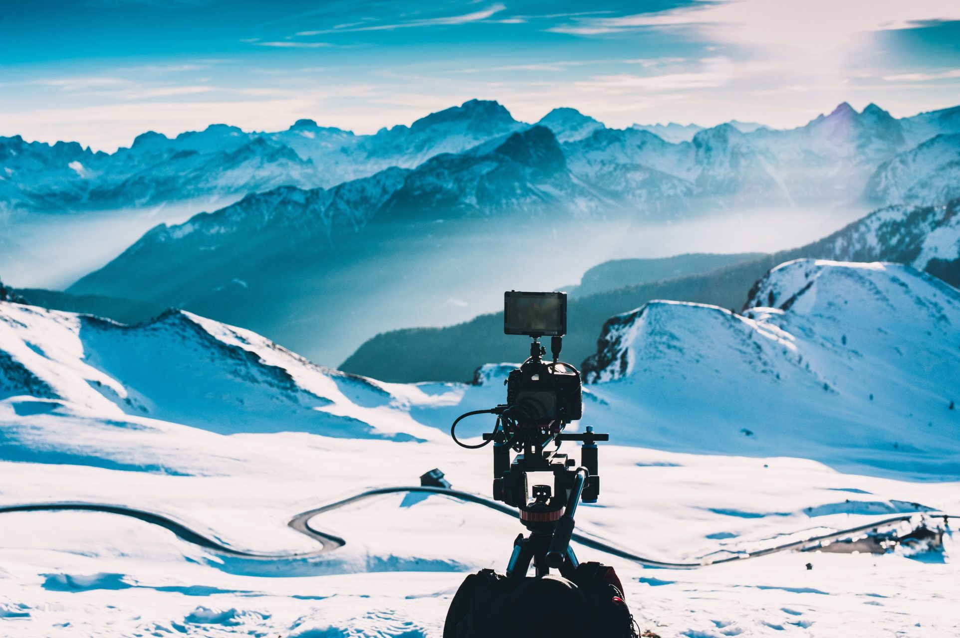 Camera tripod set up to capture the snowy mountain landscape