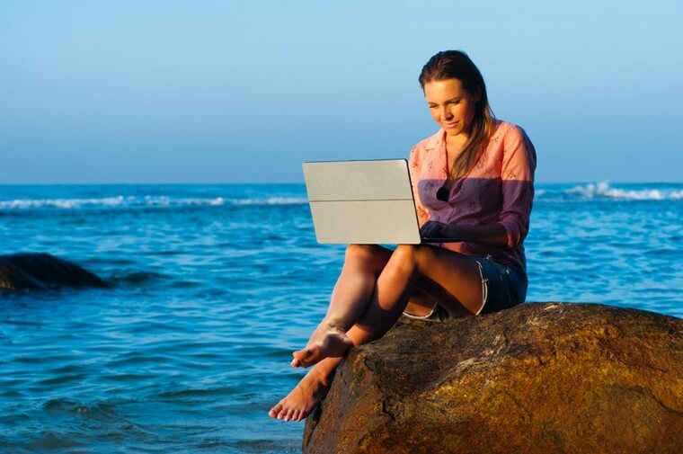 Woman typing on a laptop while sitting on a rock in the ocean