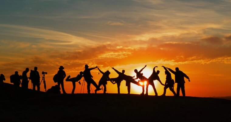 Silhouettes of people posing in front of the sunset