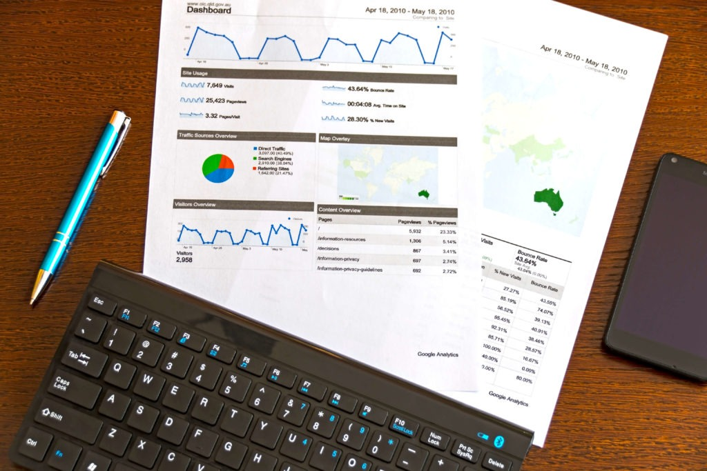Marketing reports with a focus on Australia placed on a table next to a laptop