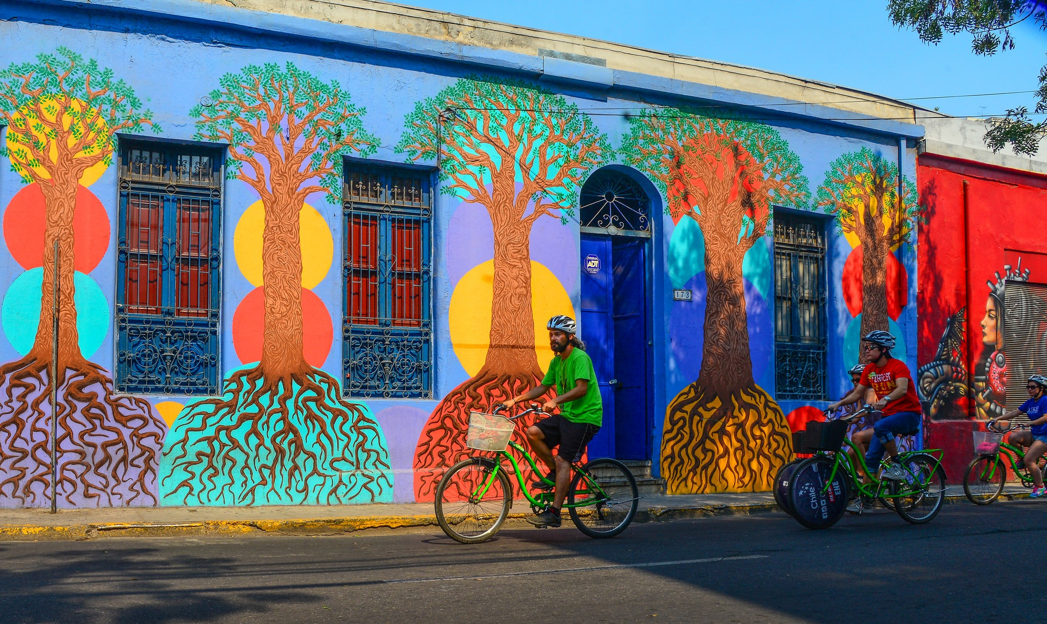 Tour group with La Bicicleta Verde biking past a colorful tree mural