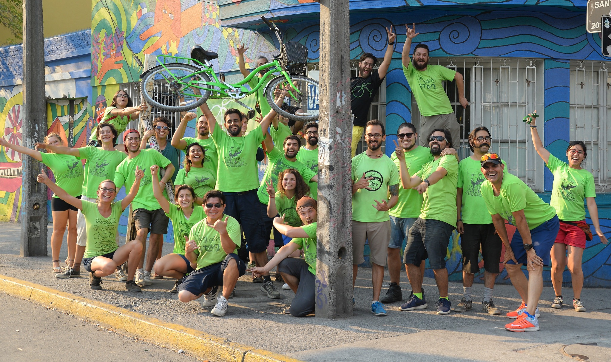 La Bicicleta Team clad in green shirts posing in front of their business building