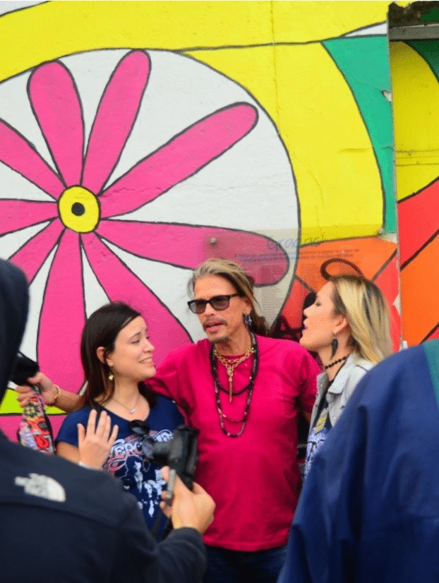 Steven Tyler posing with two women against a floral mural background