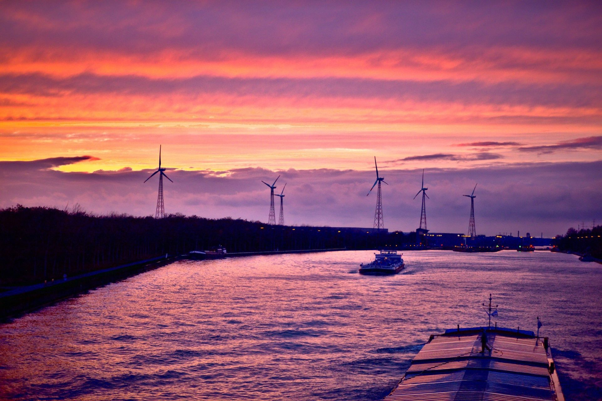 Five high-tech windmills along a river at sunset