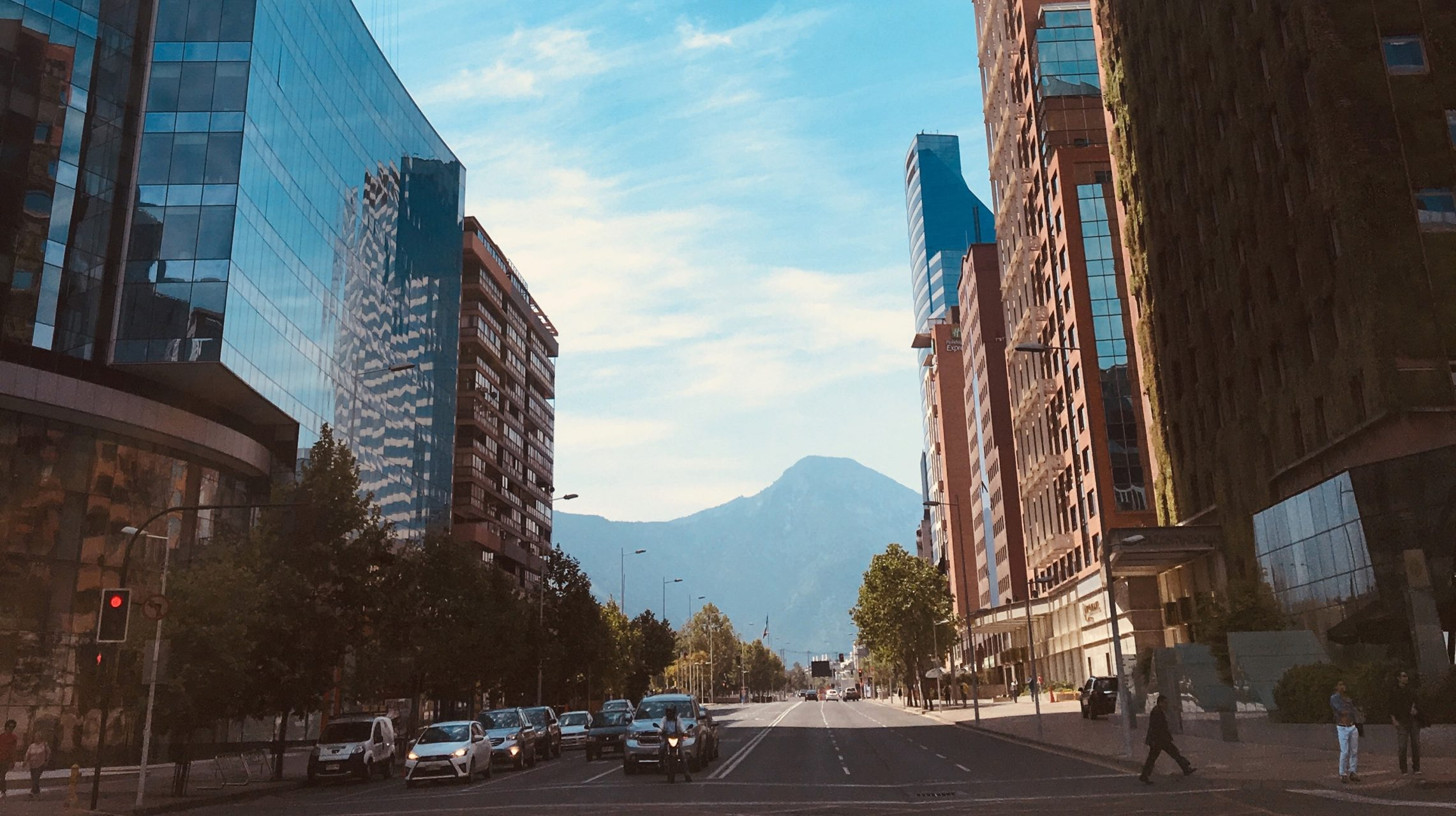Mountain in the background of tall buildings lining a street