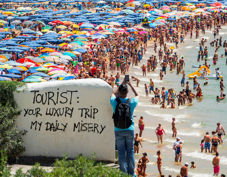 Overcrowded beach with a sign saying 'Tourist: your luxury trip, my daily misery'