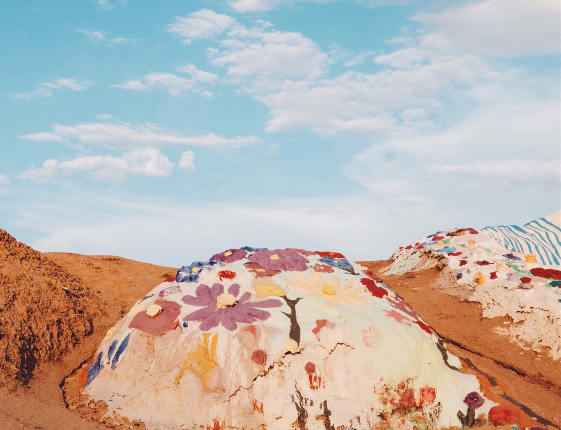 Colorful painted sand dunes beneath a blue sky