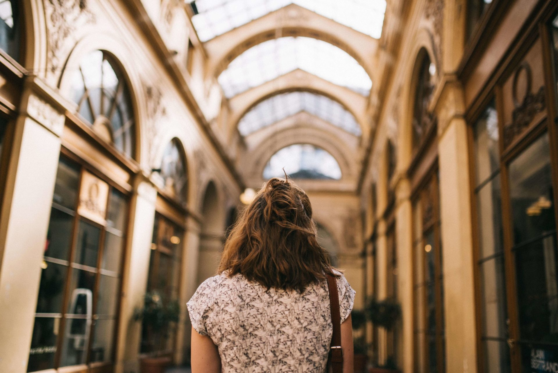 Woman staring at the atrium roof filled with windows