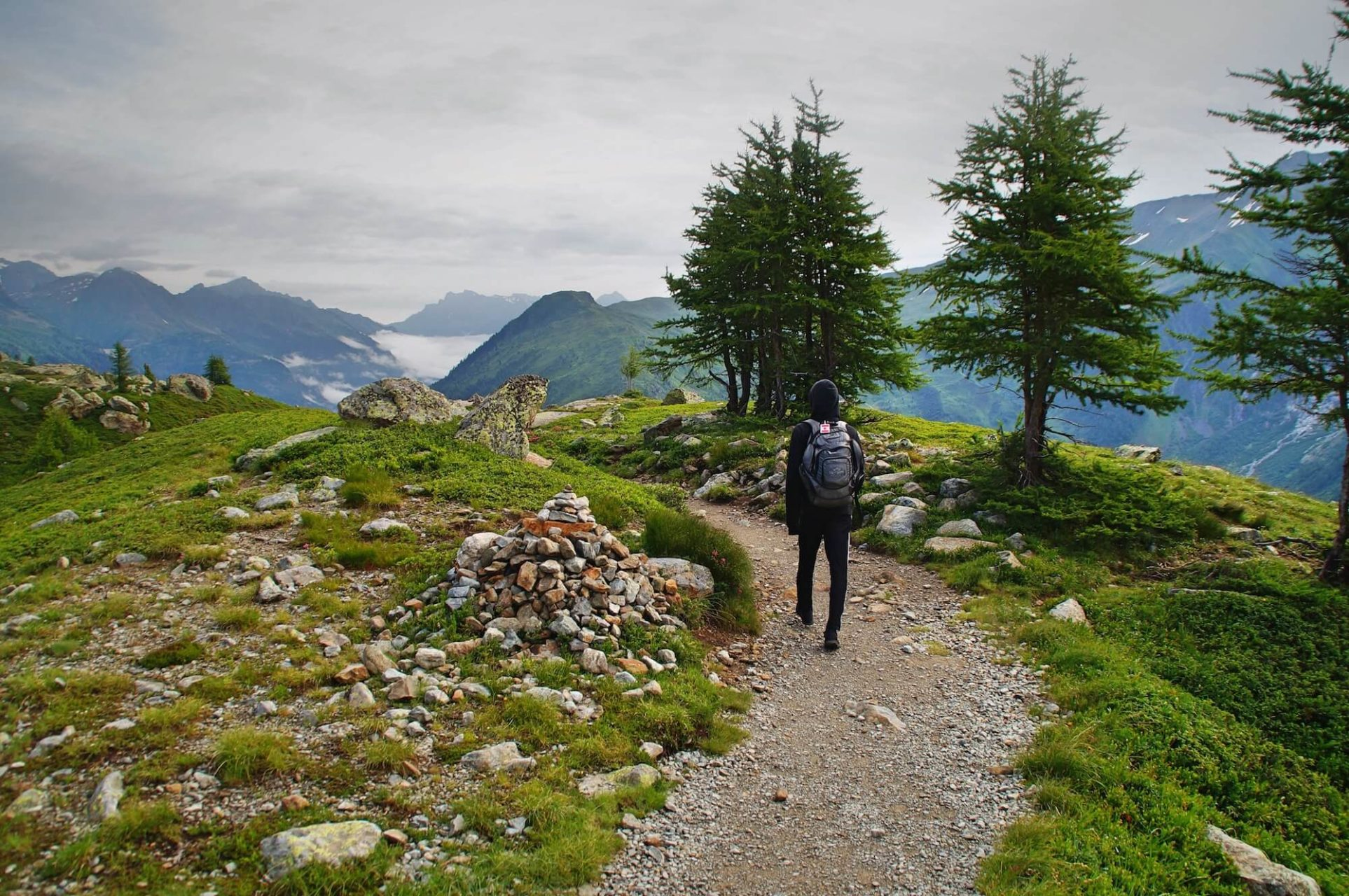 Person with hoodie and backpack on walking up a mountain trail