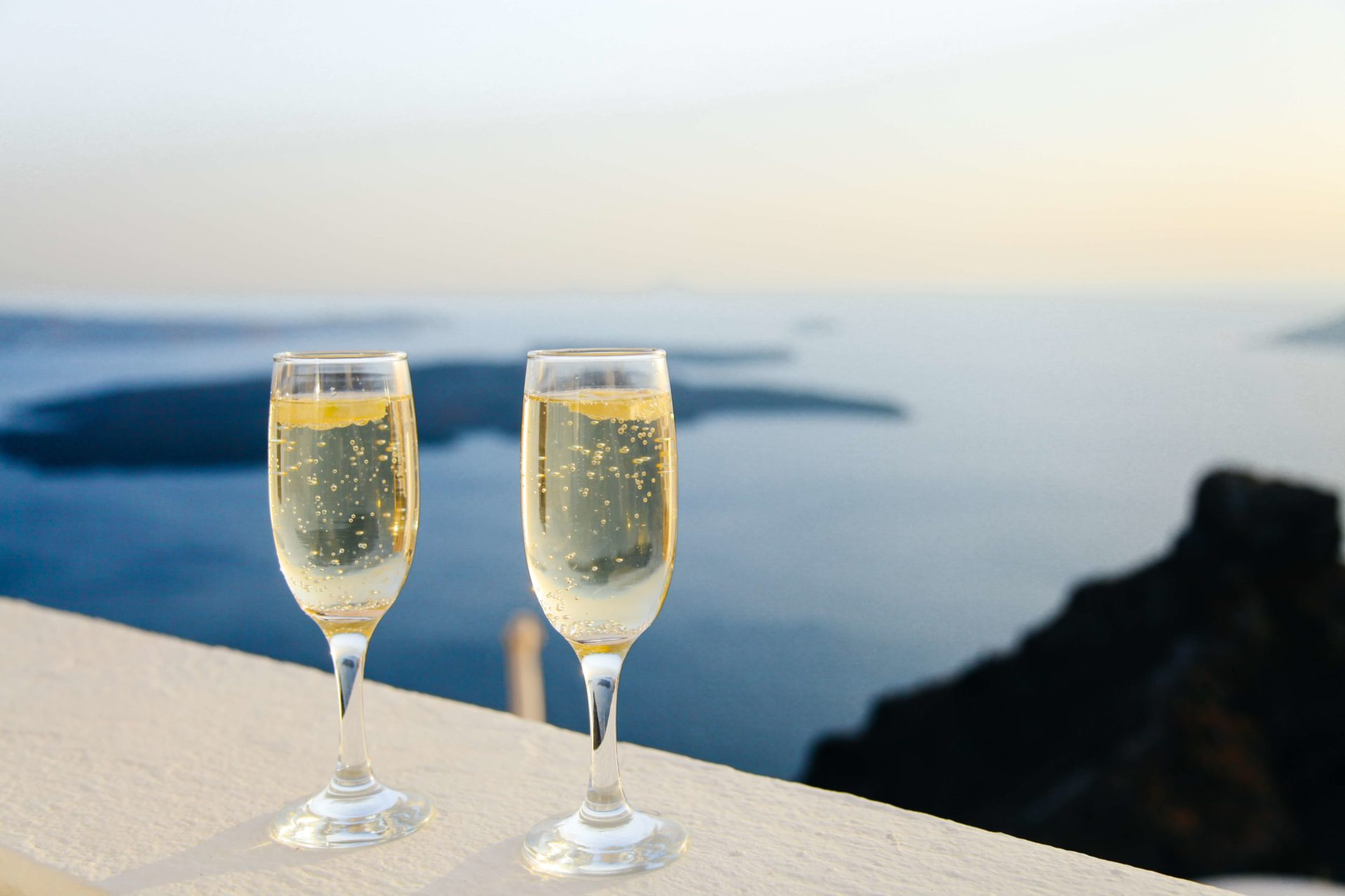 Two champagne flutes on a table overlooking the ocean