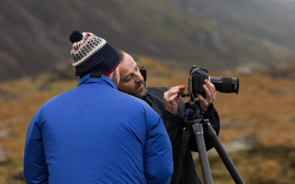 Unsplash stock photo of one man showing another man how to use a camera on a tripod