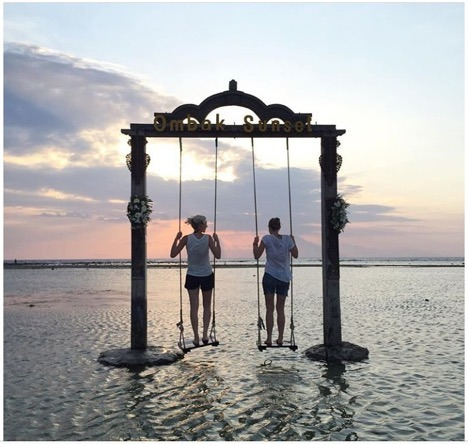 Two women standing on swings located on the ocean, swingset titled Ombak Sunset