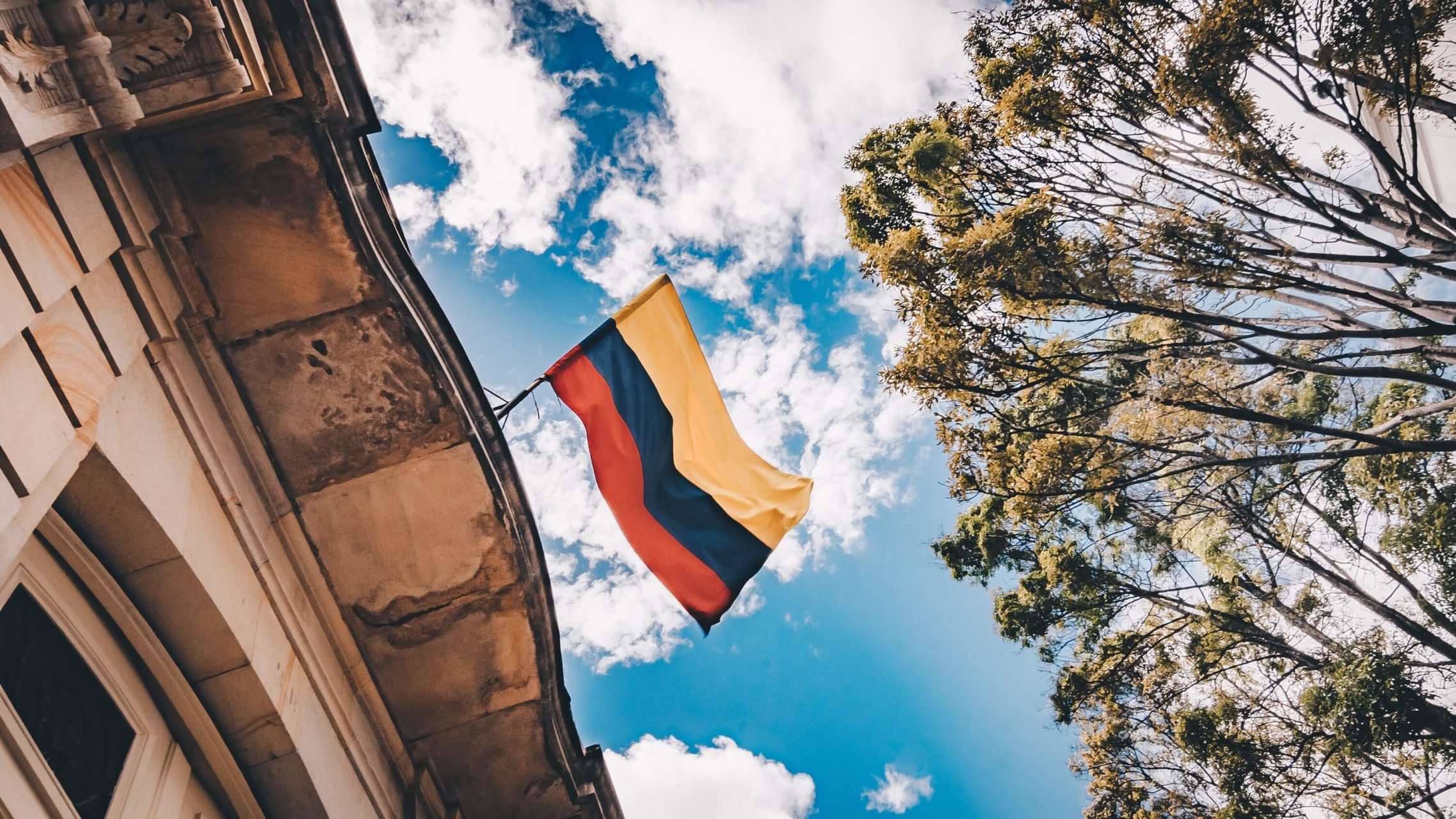 Colombian flag hung on building facade against a clear blue sky