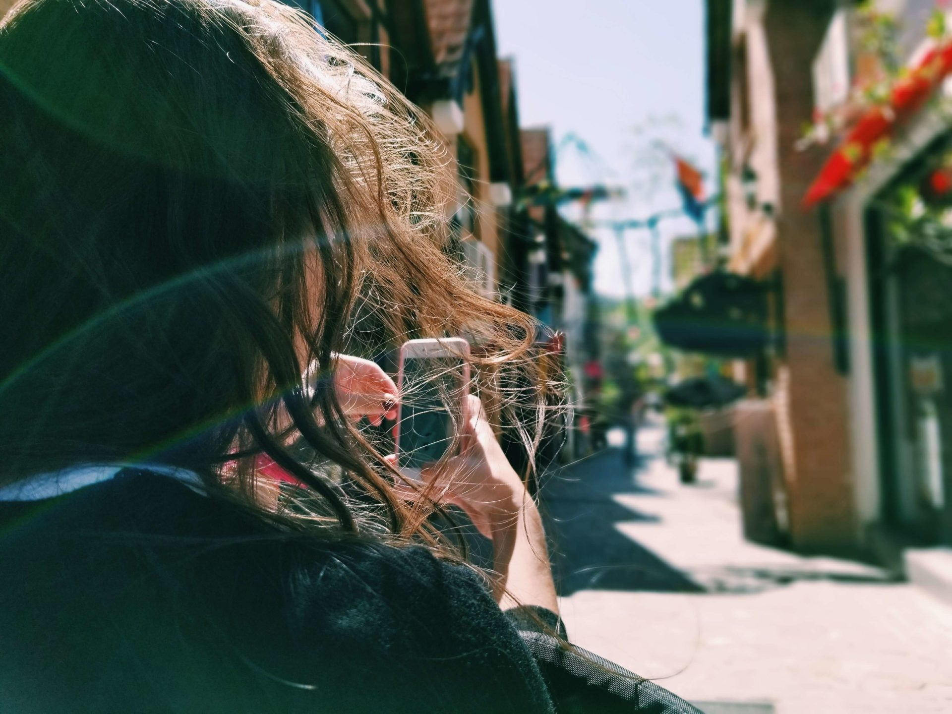 Woman holding phone camera and taking a photo while her hair blows in front of her face