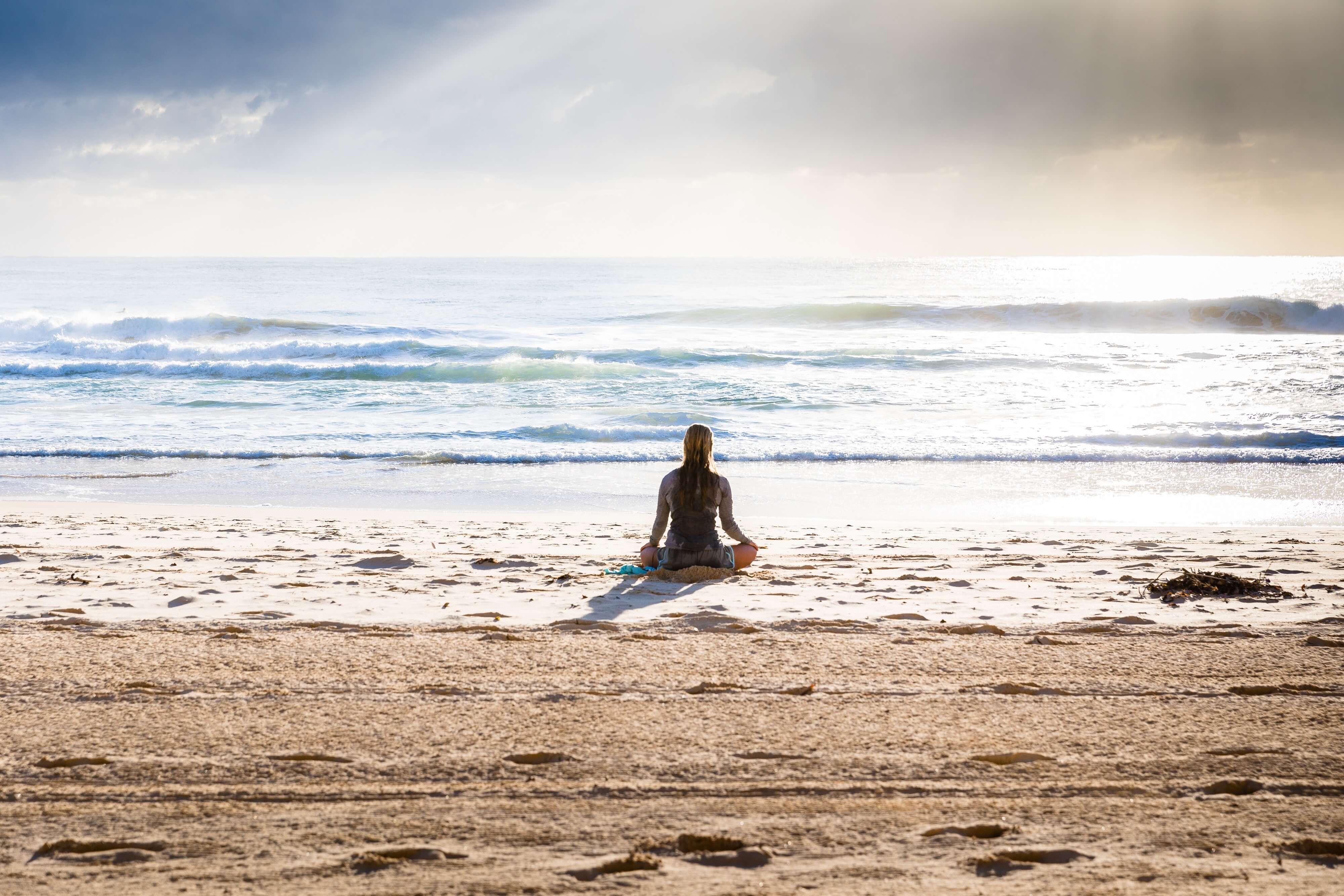 Person Sitting on Beach Near Ocean