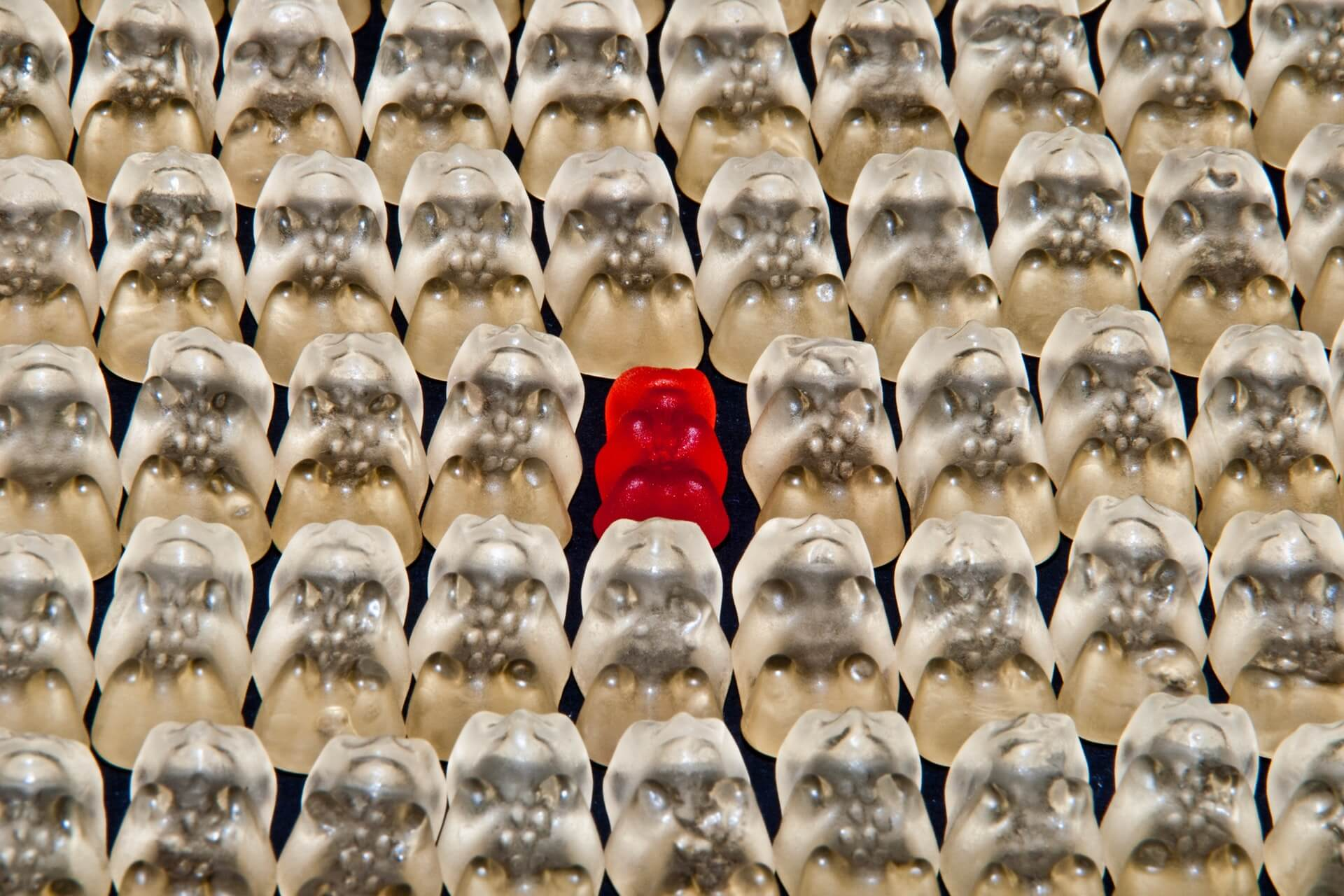 Red gummy bear in a sea of white gummy bears