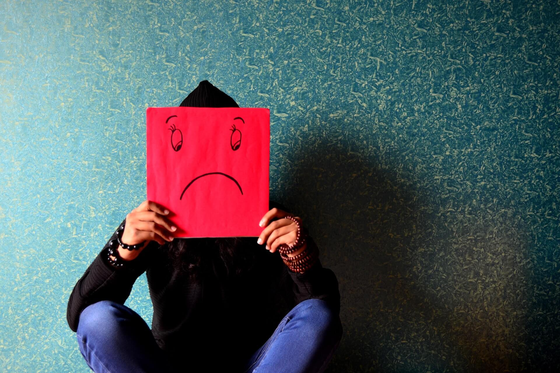 Person in a hoodie holding up a piece of red paper in front of their face with a frowny face on it