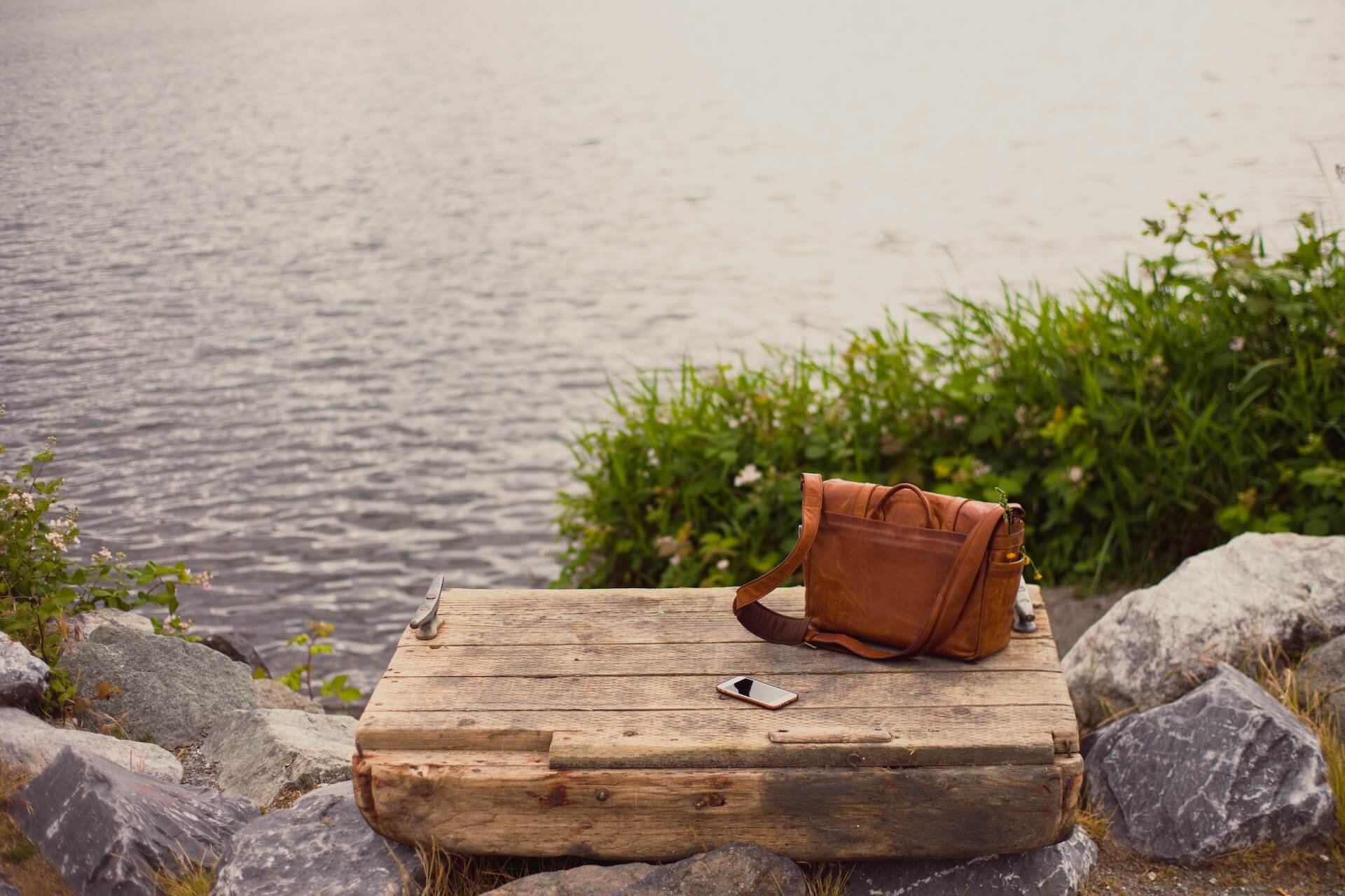 Messenger bag next to a cell phone, all atop a wooden pallet in front of a body of water