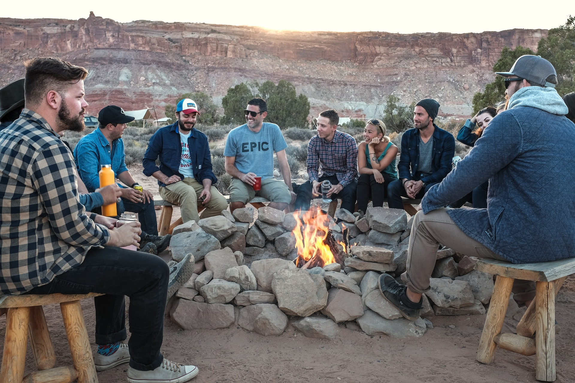 Group of people sitting around a campfire listening to one person talk