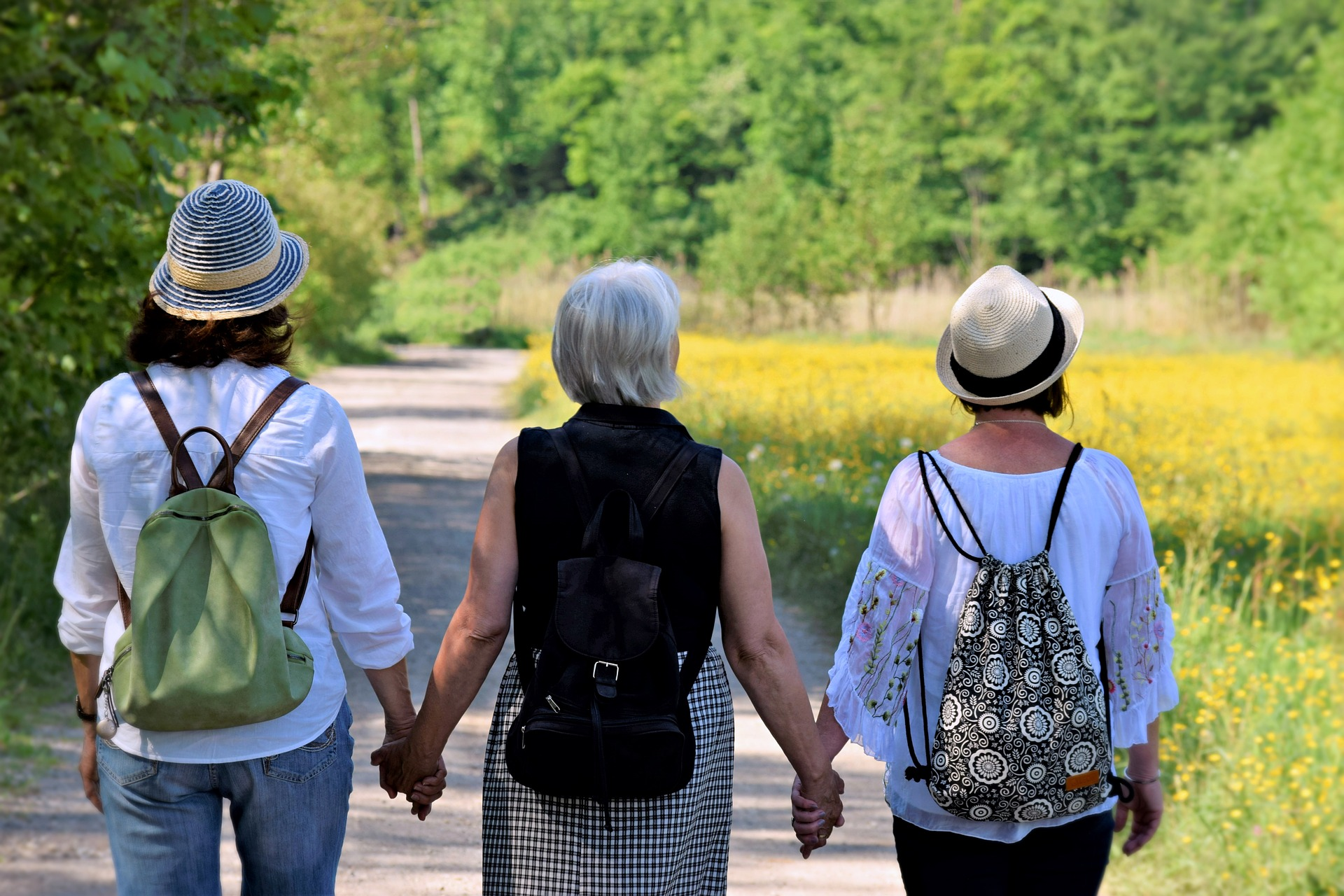 3 women of different ages walking away from the camera down a wooded path