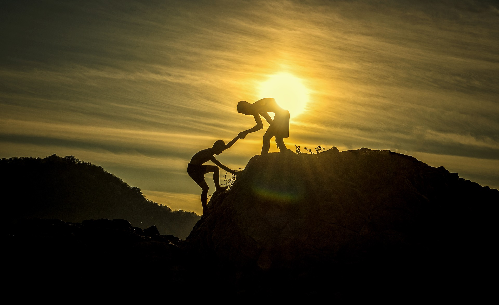 Two silhouettes climbing a hill at sunrise or sunset