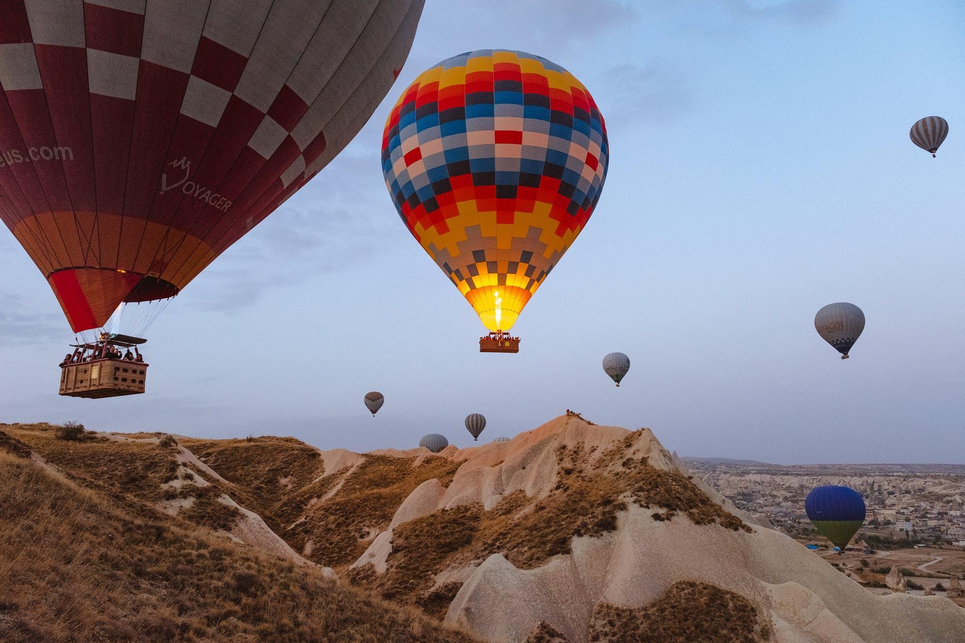 Hot air balloons rising above a desert hill