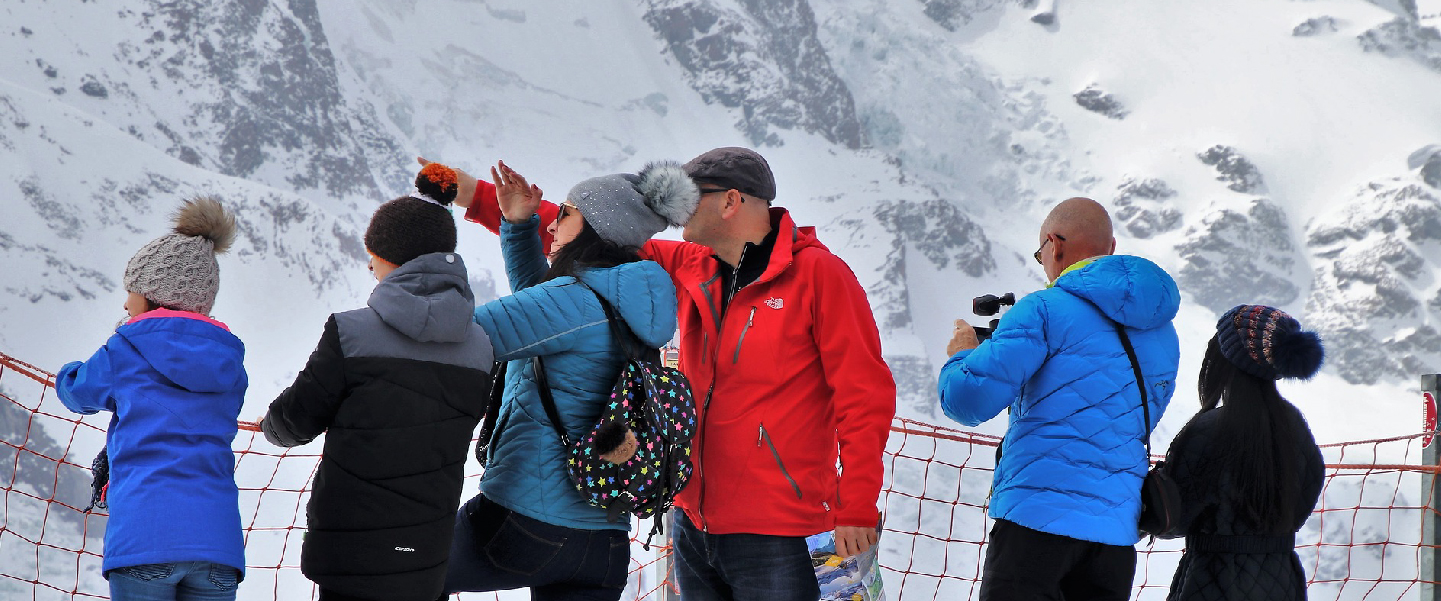 Group of people standing in front of a snowy mountain with a guide pointing out something out of frame