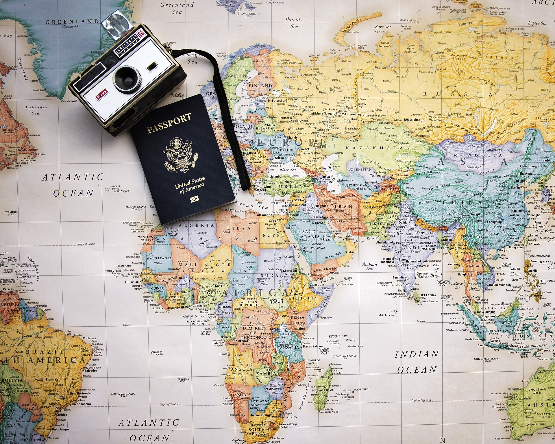 World map with a passport and camera in the top corner
