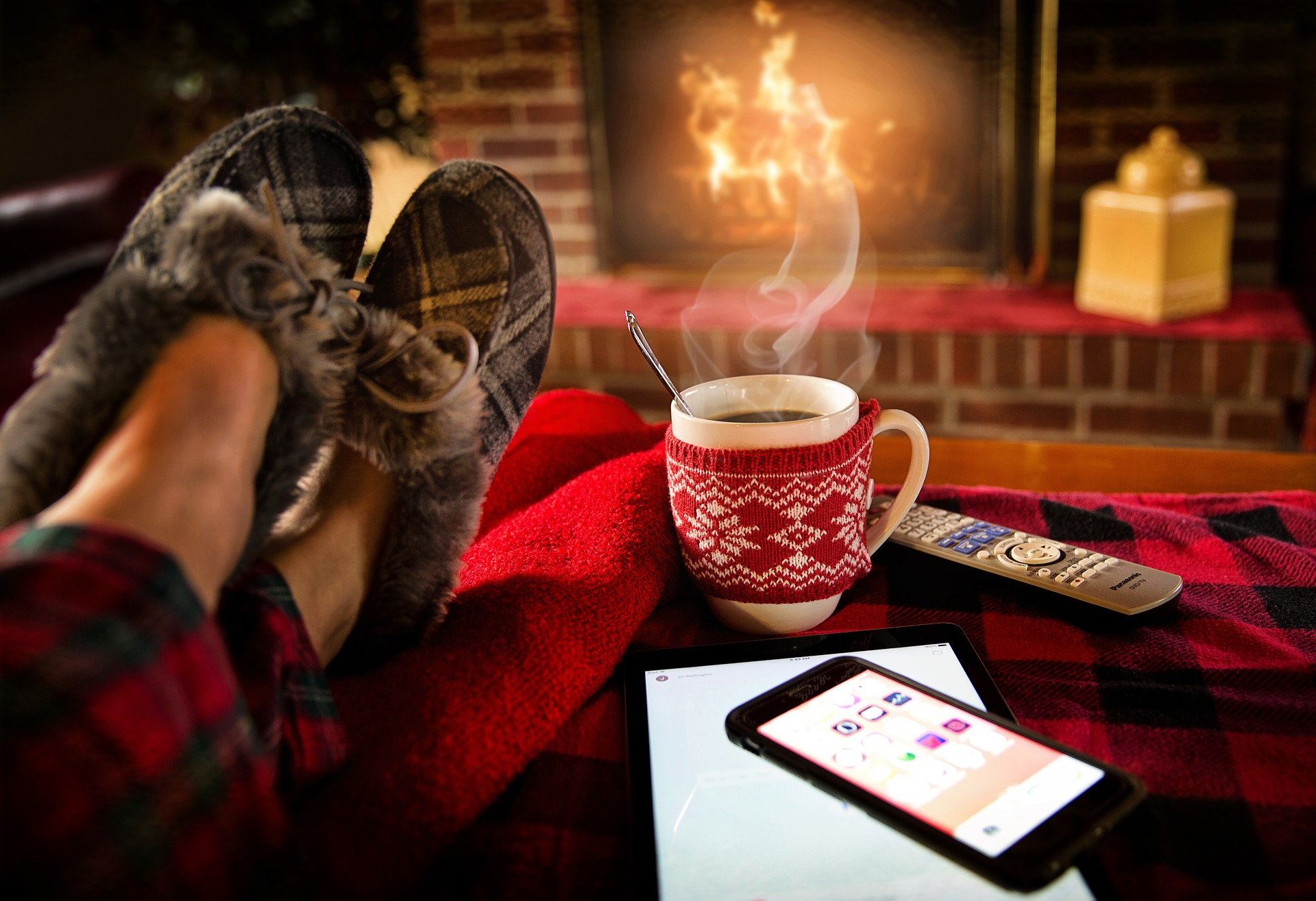 Feet in slippers put up next to a hot drink, phone, tv remote, and in front of a fireplace with a fire