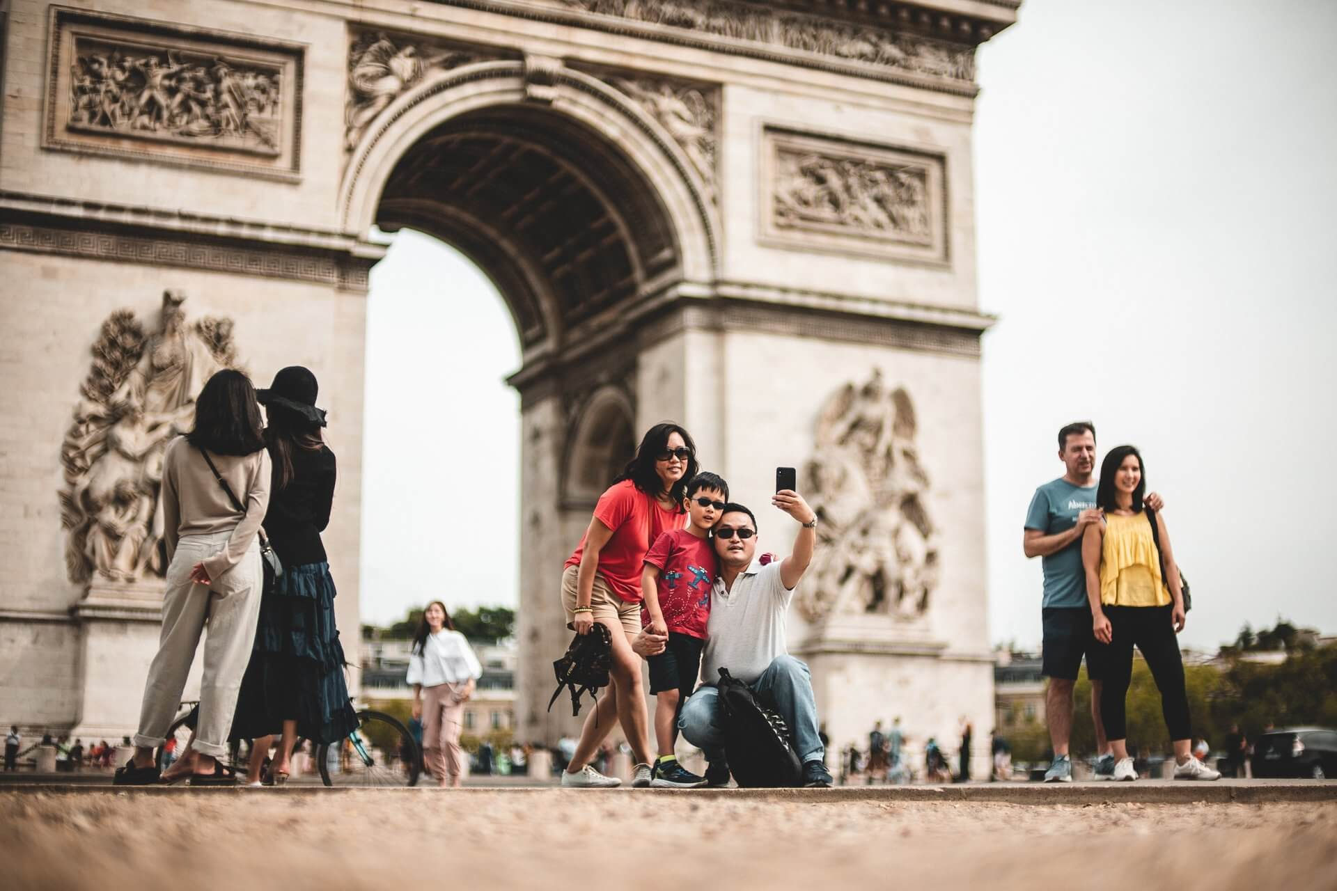 Tourists taking a selfie in frot of the Arc de Triomphe
