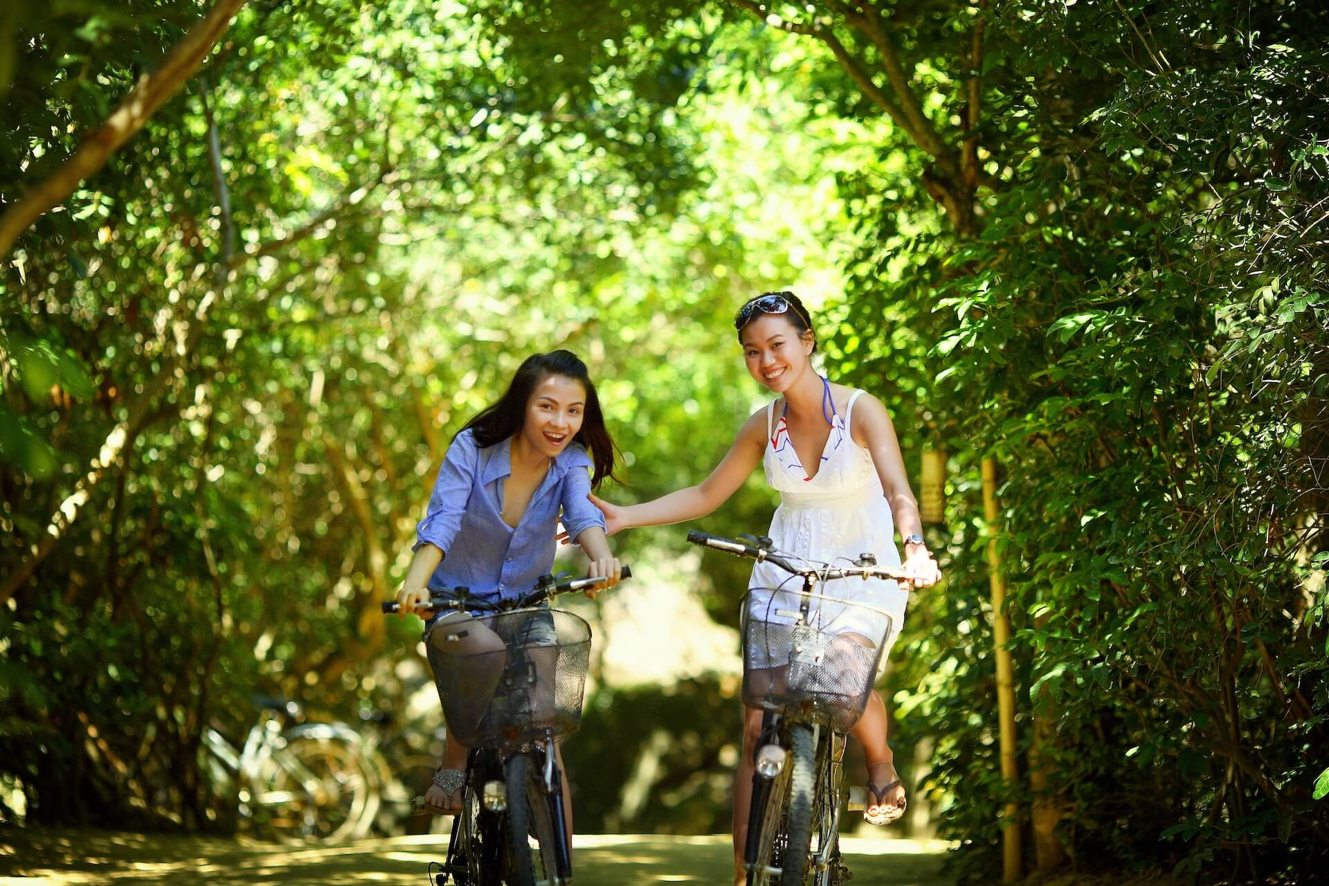 One woman in a white dress on a bike holding on to the arm of another woman in a blue button-up shirt on another bike
