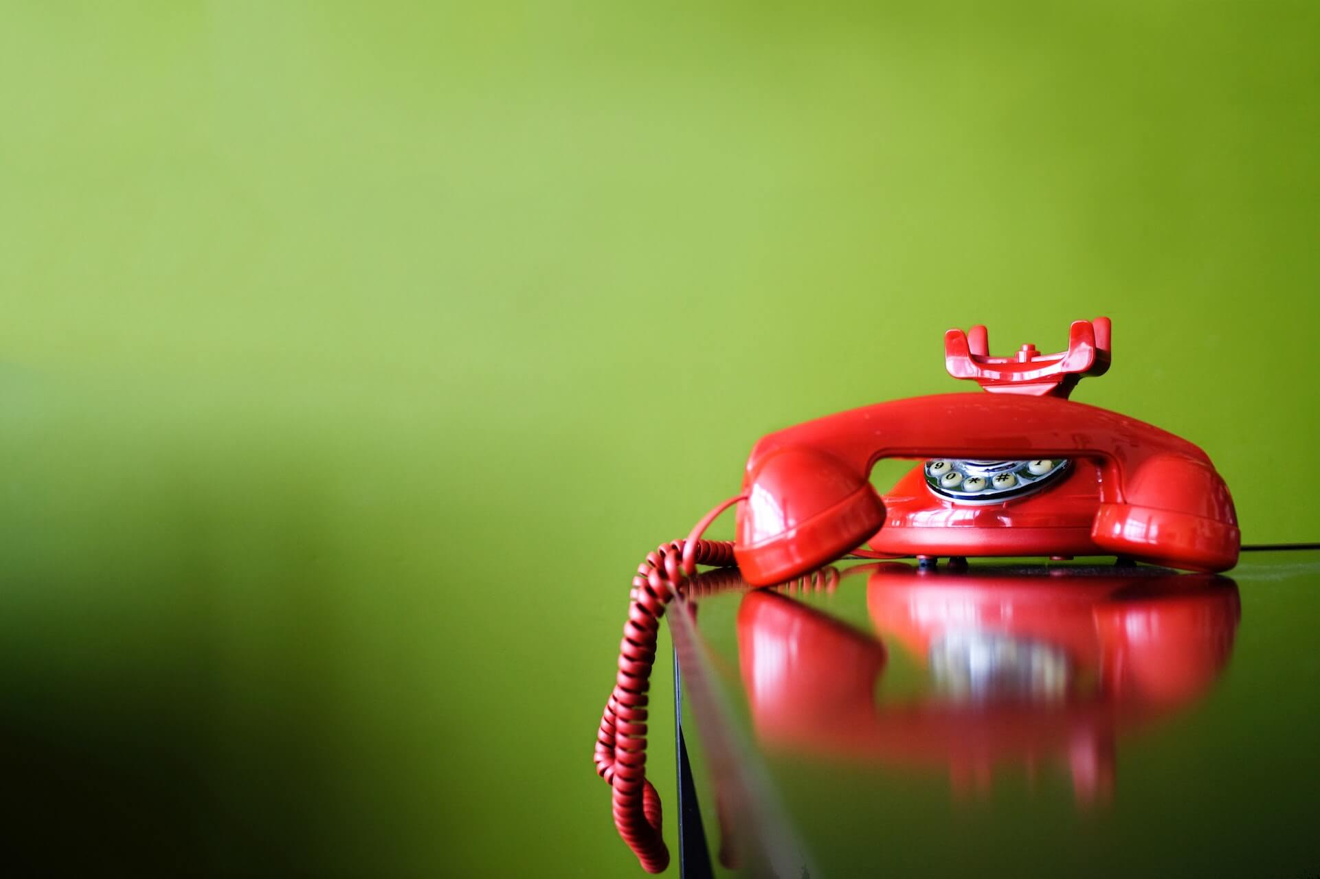 red rotary telephone on black desk in front of a green wall