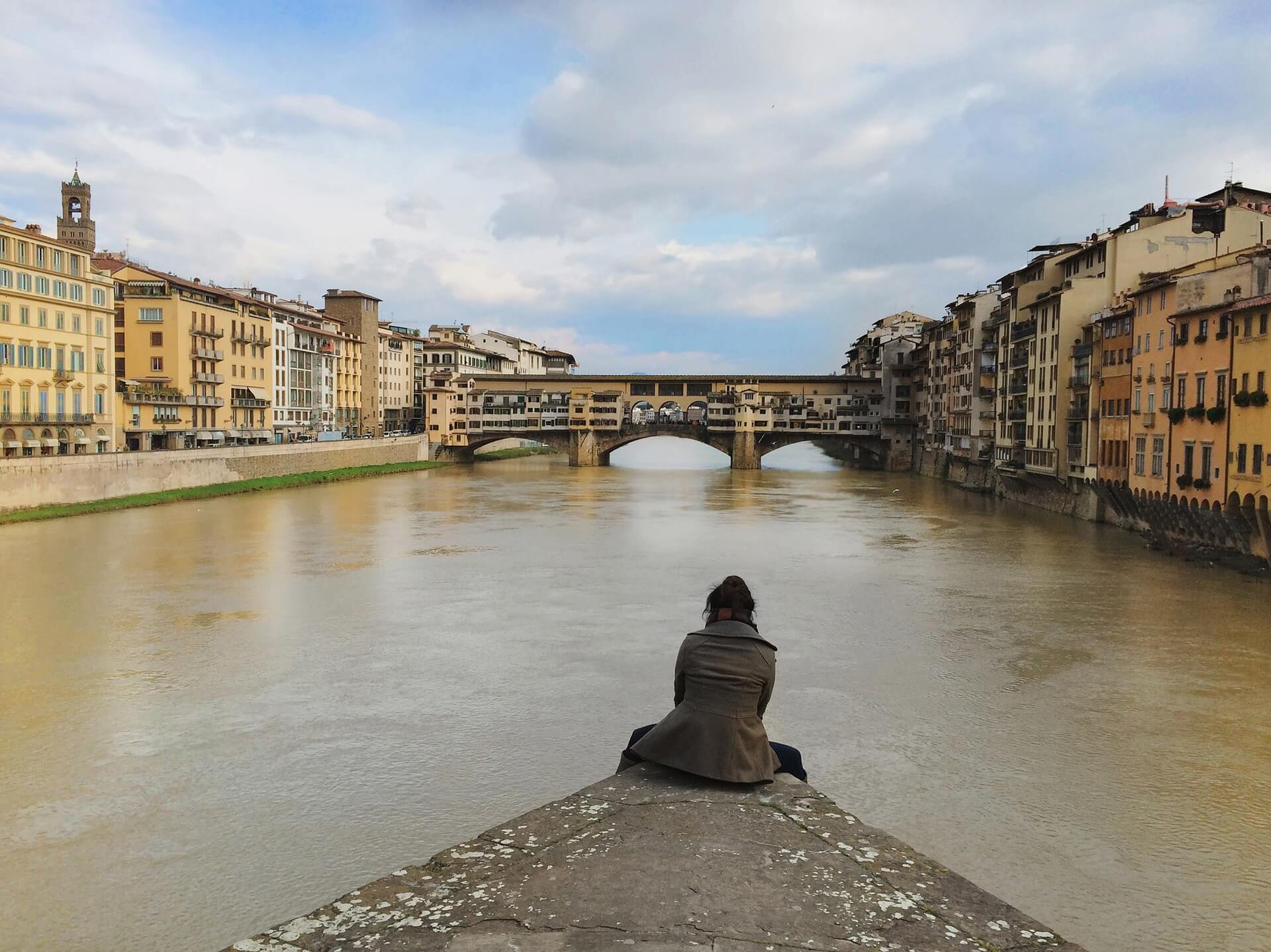 Person sitting at the end of a path, in a canal, looking at buildings