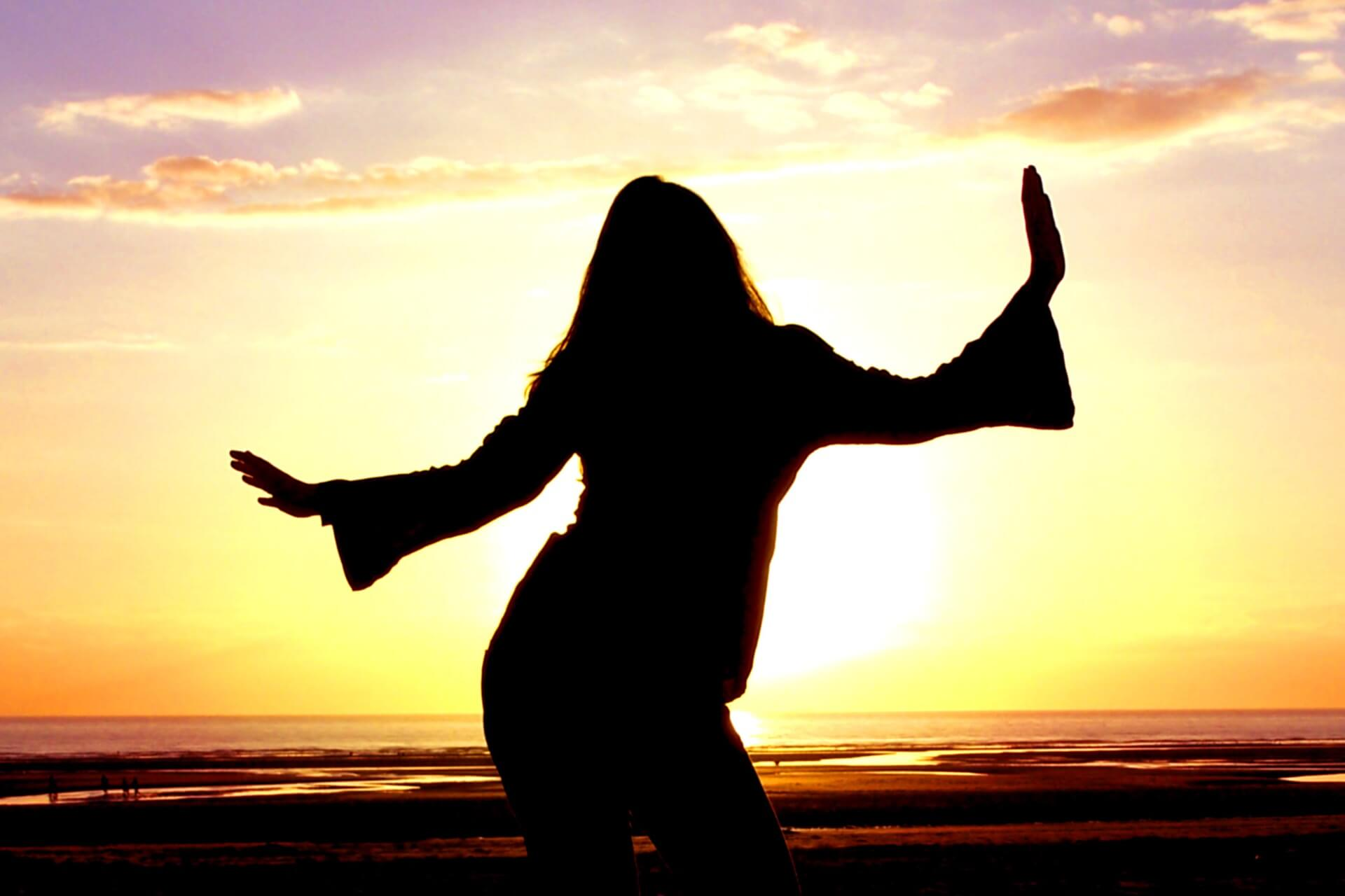 Silhouette of a woman dancing in front of a sunset