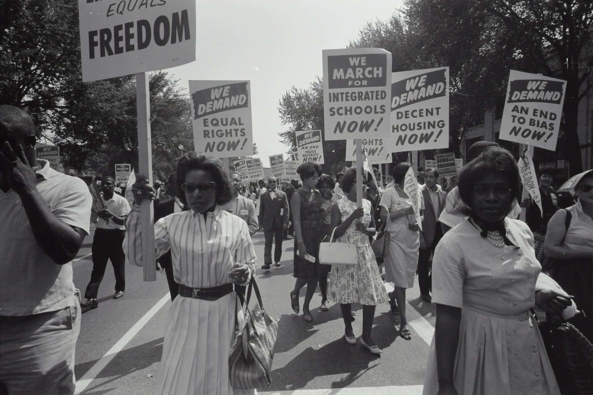 Black and white image of people marching for equal rights holding placards and signs