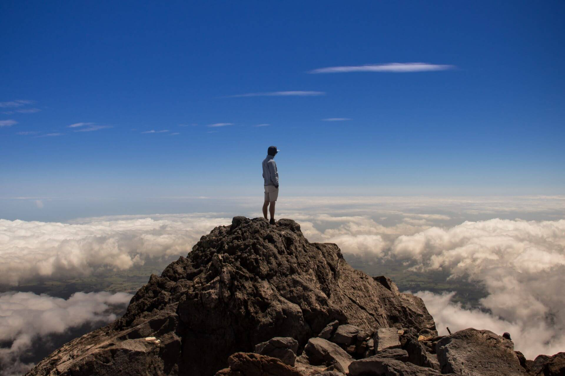 Man standing at the top of a mountain overlooking the rolling cloud and blue sky
