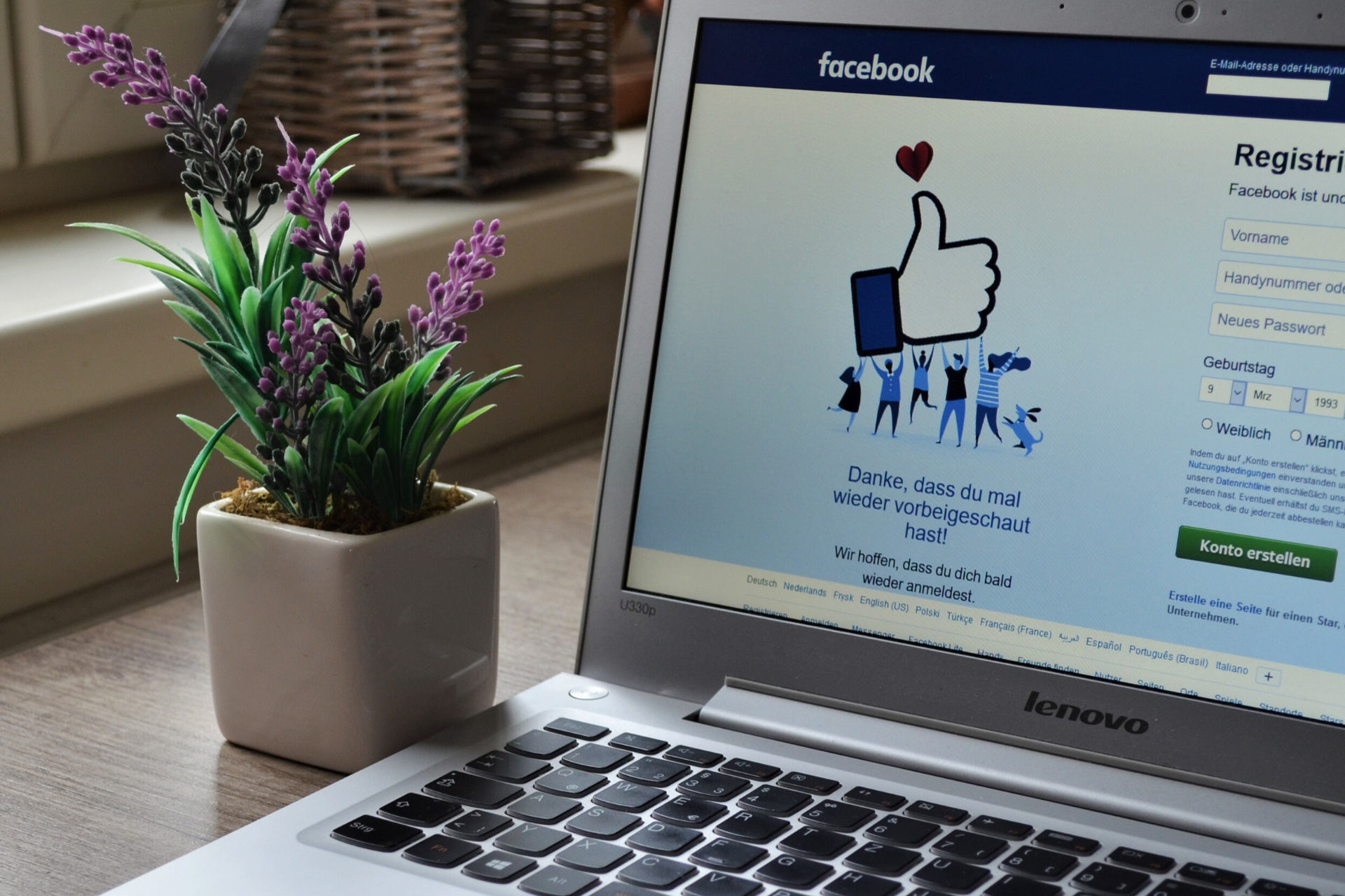 Laptop open to Facebook next to flowers