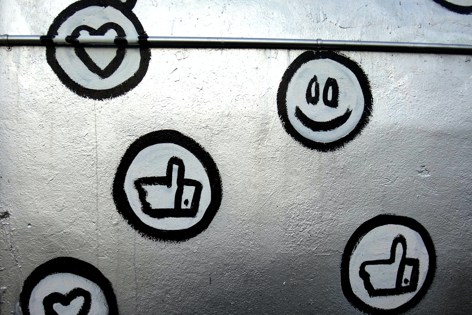 thumbs up, smiley face, and heart symbols painted on a metal background
