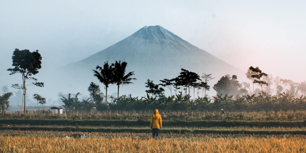 person in yellow raincoat looking at volcano in the distance
