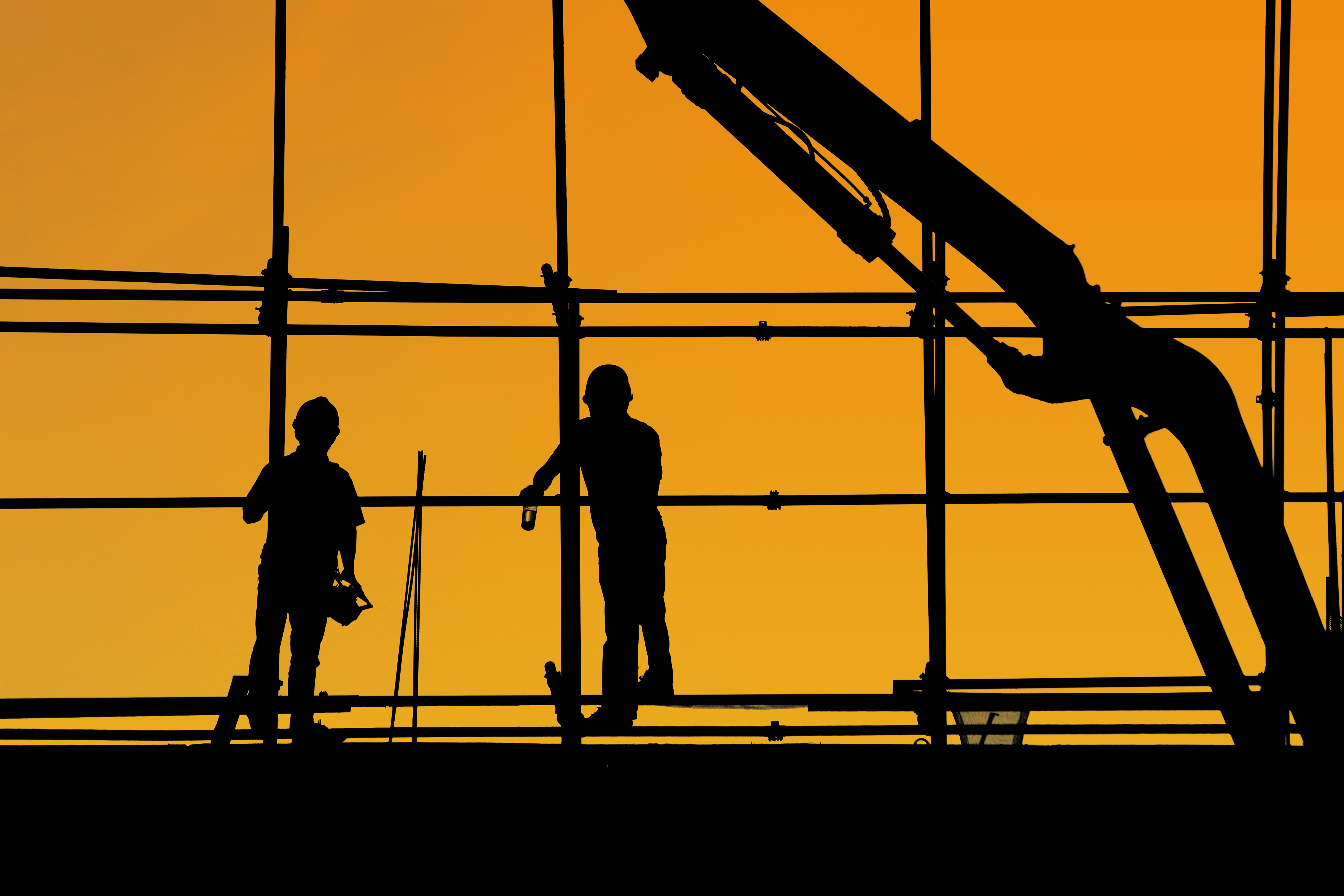 Silhouette of two construction workers