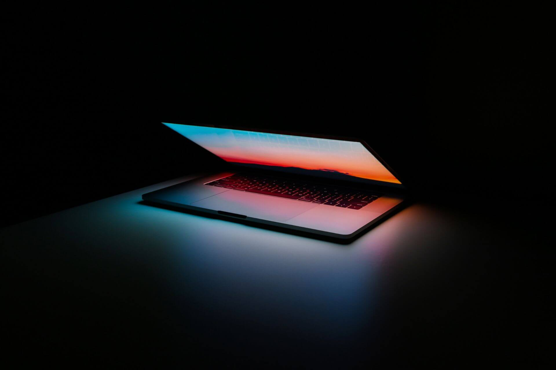 Laptop slightly opening glowing a blue and orange colour with a dark background