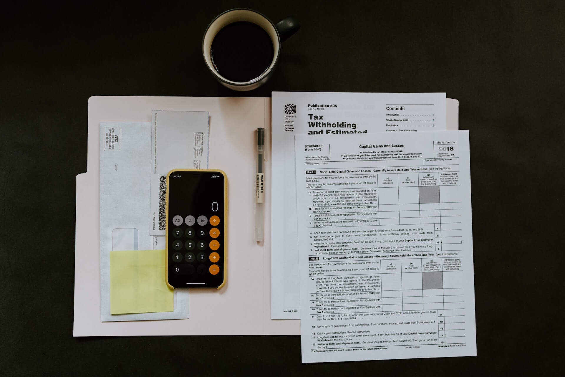 phone calculator, cup of coffee and tax forms laid out on table