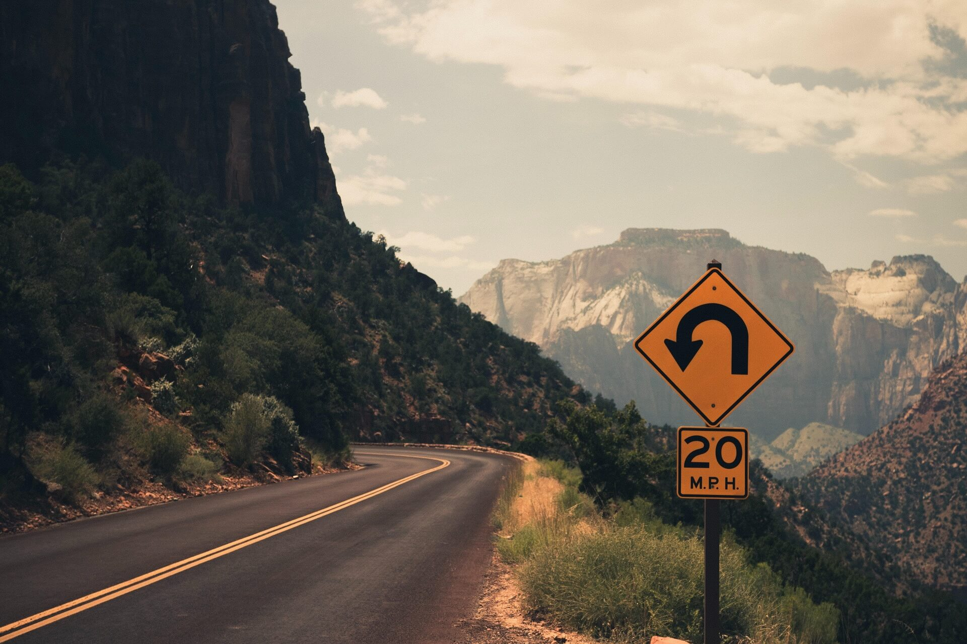 Mountain road with a sign warning the road will curve