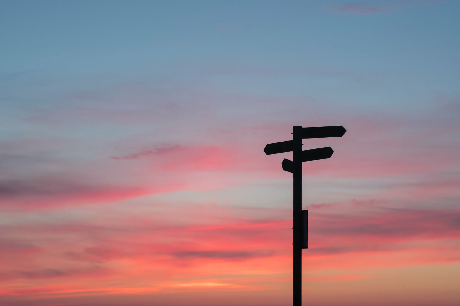 A signpost forms a silhouette against the backdrop of a sunset.