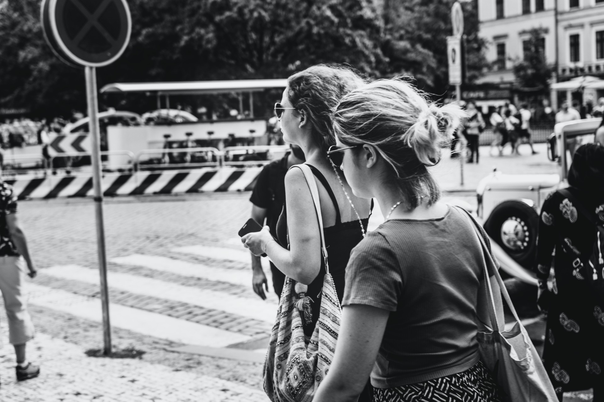 two girls crossing a busy city street in black and white